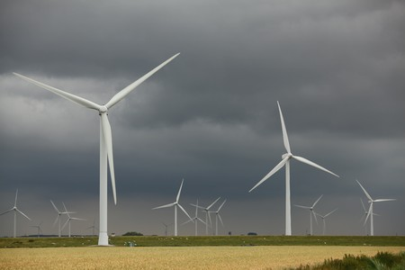 A windmill-powered plant in front of a dark and cloudy sky Stock Photo - 7492885