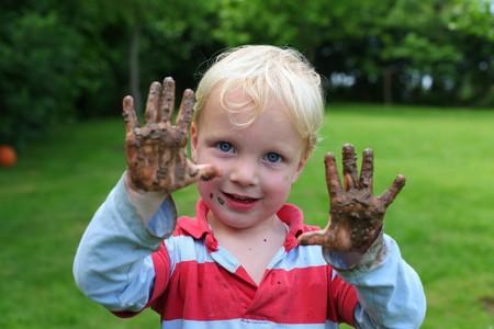 manos sucias: Chico joven muestra sus manos fangosas