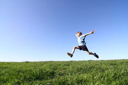 A sportive young boy makes a big jump Stock Photo