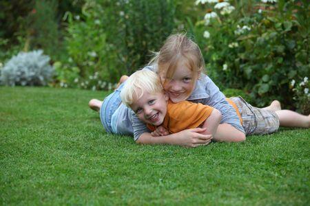 lying in grass: Risa de ni�o y ni�a jugando en el jard�n  Foto de archivo