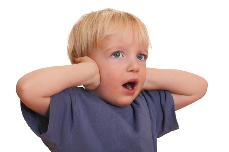 Unhappy young boy with hands on ears