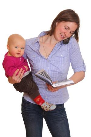 werkende moeder: Jonge moeder aan de telefoon met baby in een arm en memo blok in de andere kant Stockfoto