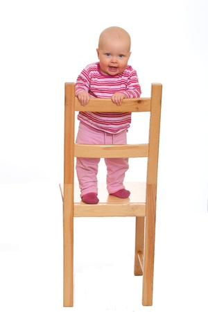 Happy baby girl standing on a chair isolated on white background photo
