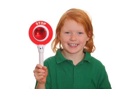 negate: Smiling red haired girl shows stop sign isolated on white background