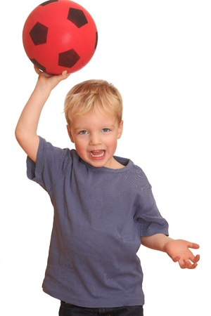 Portrait of a young boy throwing a red ball photo
