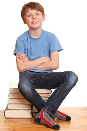Portrait of a happy schoolboy sitting on a pile of books Stock Photo - 8831414