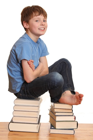 Portrait of a smiling schoolboy sitting on a pile of books Stock Photo - 8831412