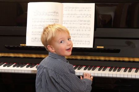 playing instrument: Portrait of a young boy playing piano