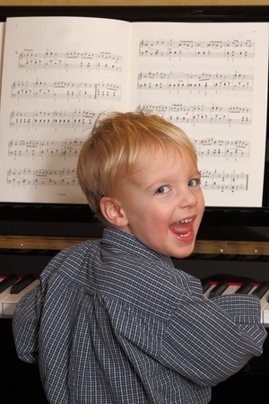 Portrait of a happy young boy playing piano photo