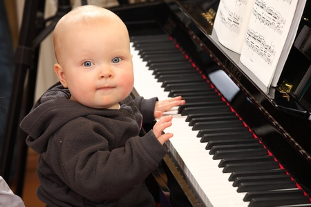 playing instrument: Portrait of a baby trying to play piano