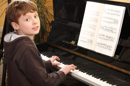 Portrait of a young teenage boy playing piano photo