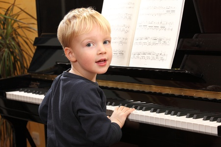 pianist: Portrait of a happy young boy playing piano