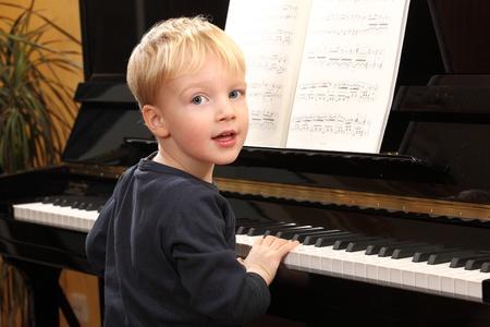 tocando piano: Retrato de un joven feliz tocando el piano