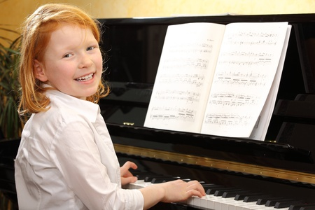 Portrait of a happy young girl playing piano