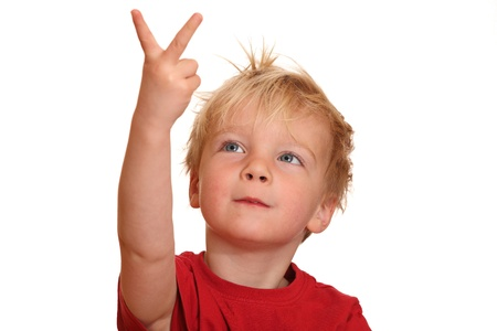 A cute little boy points with his fingers upward