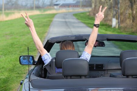 female driver: Young woman driving a sports cabriolet car