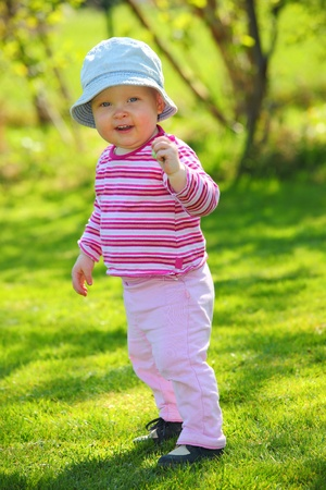 Young adorable baby walking in the garden photo