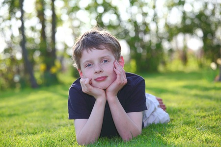 Relaxed boy lying on grass photo