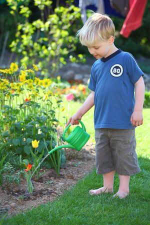 Portrait of a young boy watering the flowers in the garden