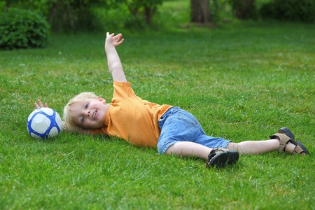 Young boy playing with a ball in the garden photo