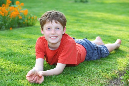 Portrait of a young boy lying in the grass
