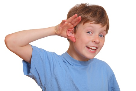 listen ear: Boy listening with attention holding hand at ear
