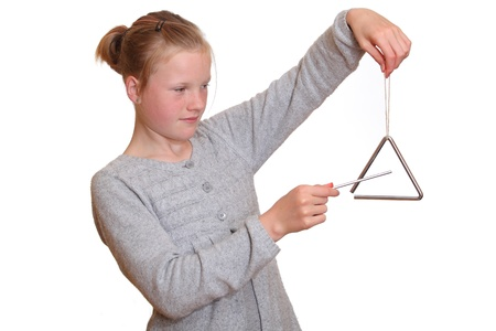 triangle musical instrument: A young girl plays with a triangle Stock Photo