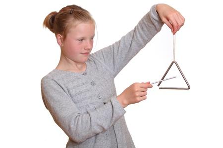 instrumentos musicales: Una ni�a juega con un tri�ngulo Foto de archivo