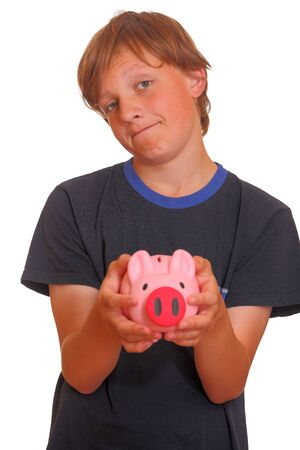 Portrait of a skeptical looking boy holding his piggy bank on white background photo