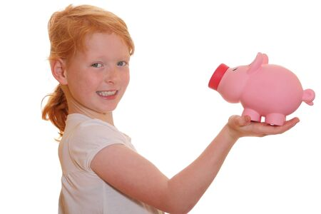 Portrait of a funny smiling red haired girl holding her piggy bank photo