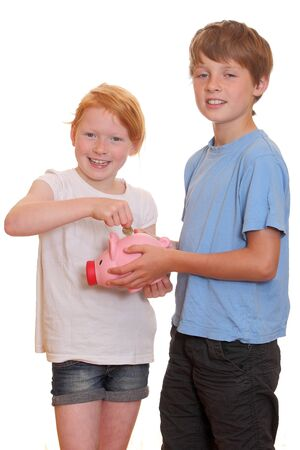 Portrait of two young kids putting a coin into a piggy bank photo