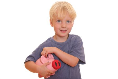 Portrait of a young blond boy holding his piggy bank photo