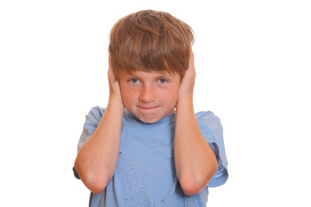 Portrait of a young boy covering his ears on white background