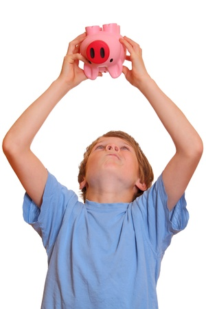 Portrait of a teenage boy trying to empty his piggy bank Stock Photo