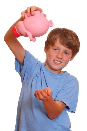 Portrait of a desperate teenage boy trying to empty his piggy bank photo