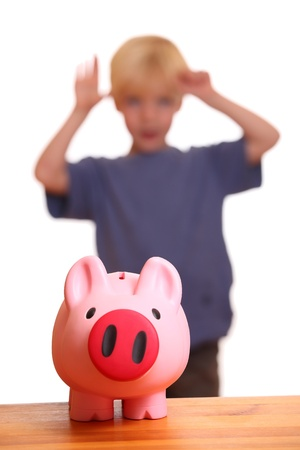 A pink piggy bank on front of a young boy photo