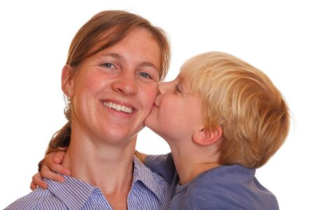 Portrait of a young boy kissing his mother on white background photo