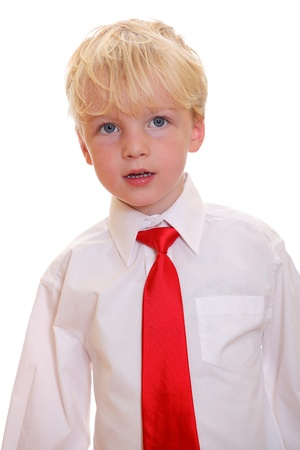 Portrait of a young blond boy wearing a red tie on white background photo