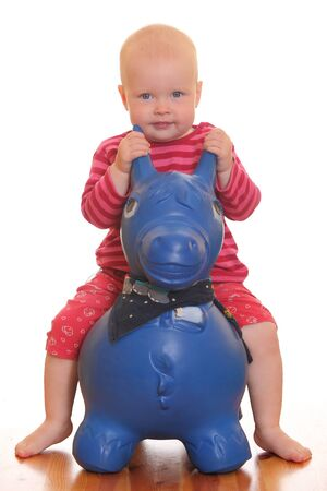 Portrait of a baby girl riding on a toy horse photo