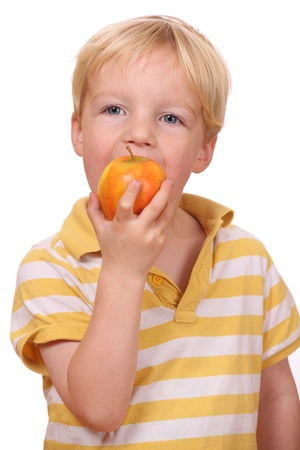 Portrait of a young boy eating an apple photo