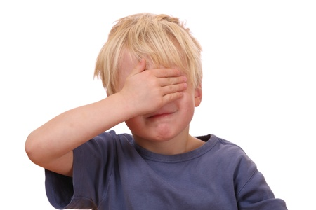 covering eyes: Portrait of a frightened young boy covering his eyes