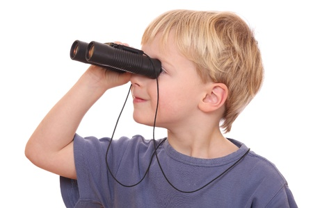 Portrait of a little boy looking through binoculars on white background