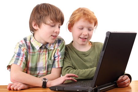 Boy and girl working together on a laptop computer photo