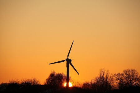Silhouette of a single windmill at sunset photo