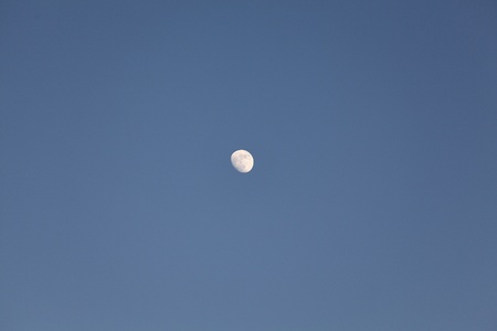 Empty blue sky with a tiny moon in center photo