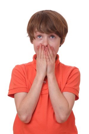 Portrait of a frightened boy covering his mouth photo