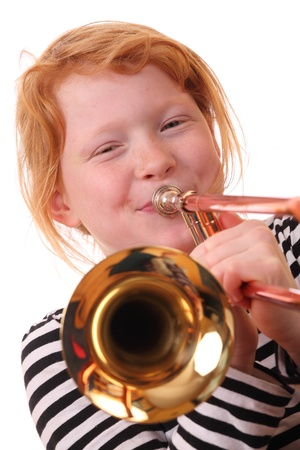 Young girl playing a trombone on white background photo