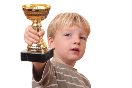 Proud young boy holding his trophy on white background photo