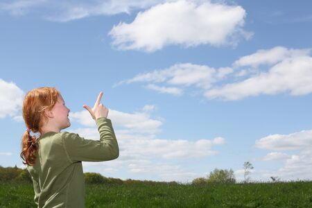 Young girl outside pointing to the sky photo