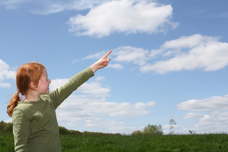 woman pointing: Young girl outside pointing to the sky Stock Photo